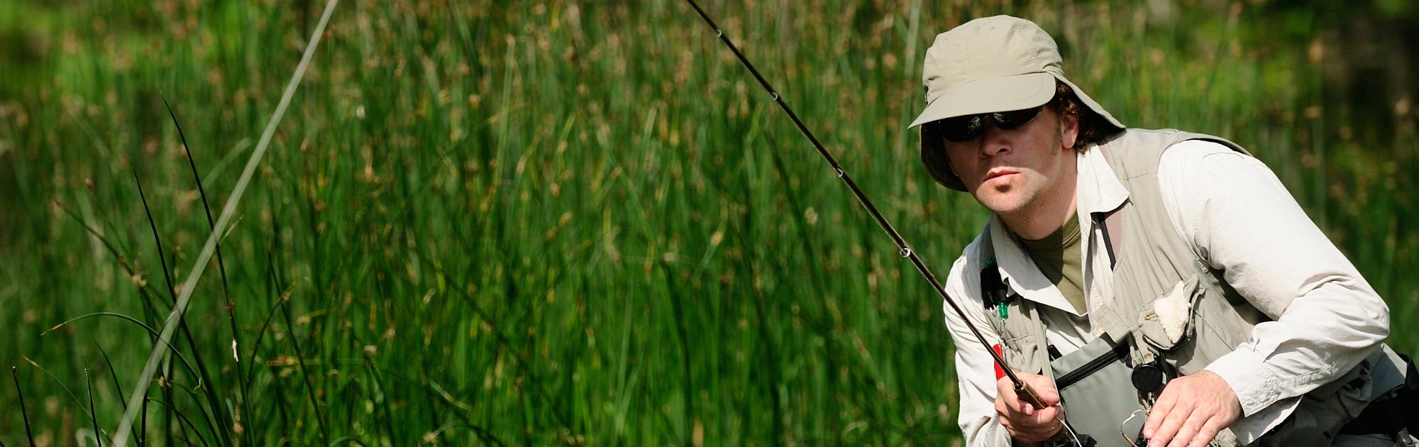 Man fly fishing wearing sunglasses