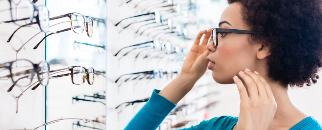 Woman trying on glasses in an opticians